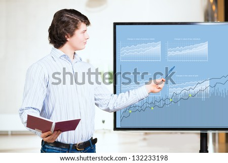 young business man shows on the monitor financial growth charts, making presentations