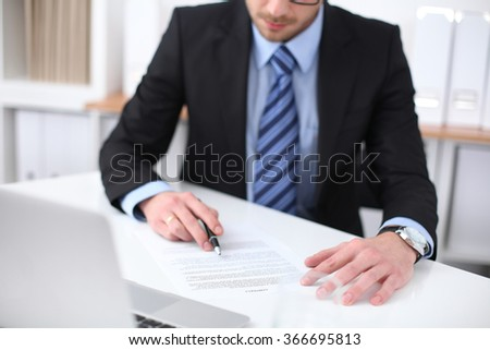 Young business man signs contract sitting at the desk in office