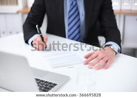 Young business man signs contract sitting at the desk in office - stock photo
