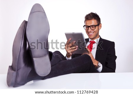 young business man sitting at his desk and reading on his electronic tablet pad - stock photo