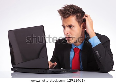 young business man sitting at the desk and looking baffled at his laptop