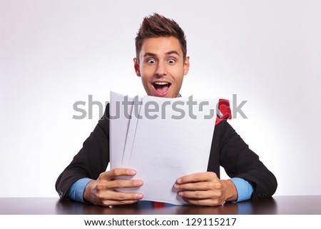 young business man sitting at the desk and reading some exciting news