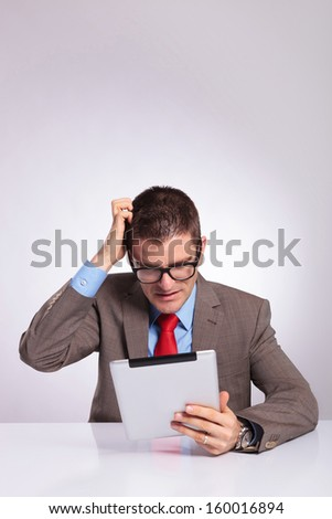 young business man sitting at the desk with a tablet in his hand and scratching his head while reading something. on a gray background - stock photo