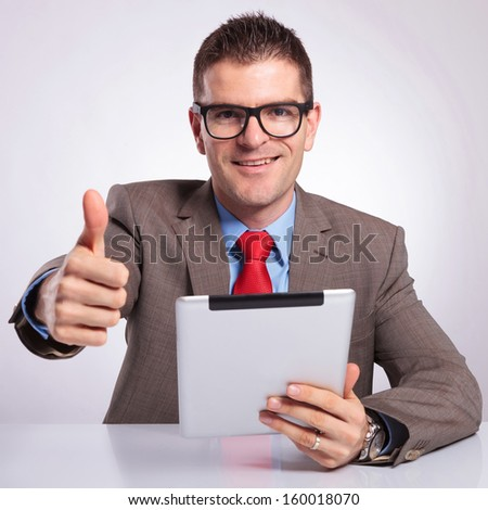 young business man sitting at the desk with a tablet in his hand and showing the thumb up gesture while smiling for the camera. on a gray background
