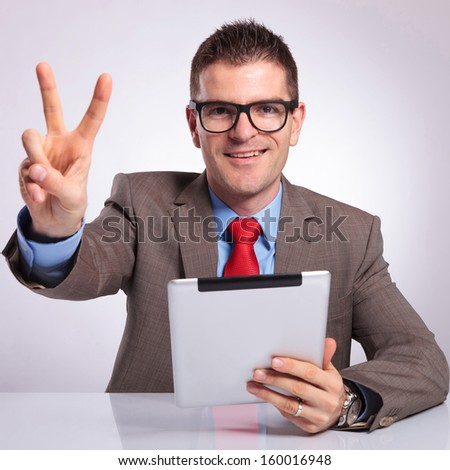 young business man sitting at the desk with a tablet in his hand and showing the victory sign while smiling for the camera. on a gray background