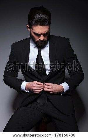 young business man sitting on a chair and buttoning his suit jacket while looking down, away from the camera. on a dark background - stock photo
