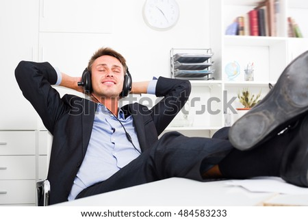 Young business man sitting with feet on desk and listening to music in company office
