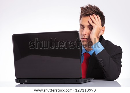 young business man sleeping in front of his laptop