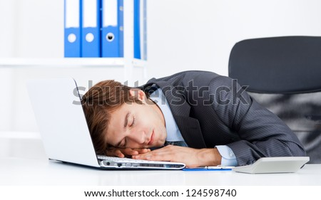 young business man sleeping on his laptop resting on workplace during work day, businessman relaxed sitting at office lying on desk with closed eyes, concept of workout, exhausted sleep, tired - stock photo