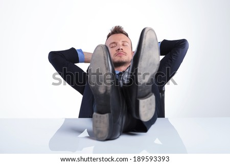 young business man sleeping with his feet on the desk and his hands behind his head. on a light gray studio background
