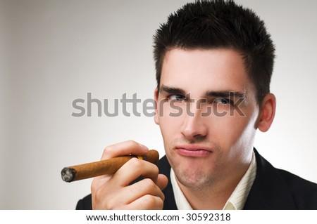 Young business man smoking cigar close up shoot - stock photo
