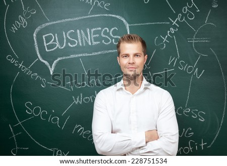 Young business man standing in front of a blackboard with a business plan