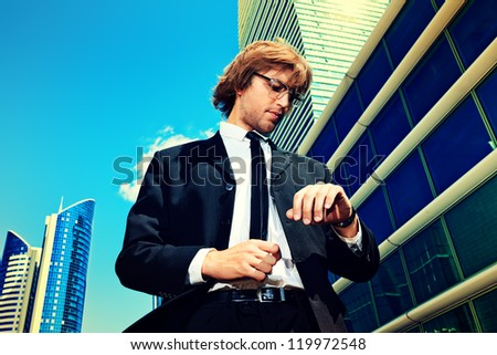 Young business man standing in the big city and looking at his wristwatch. - stock photo