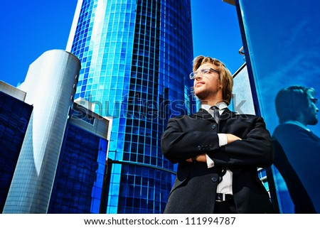Young business man standing in the big city and purposefully looking away.