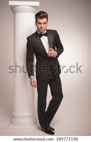 Young business man standing on grey studio background fixing his jacket. - stock photo