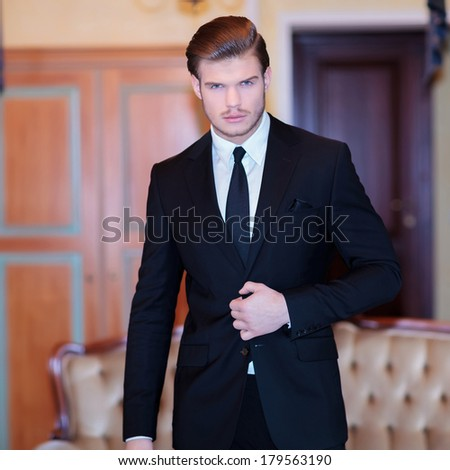 young business man standing with a hand on his suit jacket while looking into the camera, in a vintage hotel room