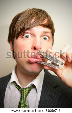 young business man staples his mouth shut - stock photo