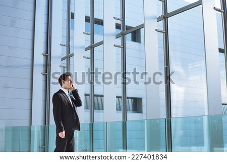 young business man talking by phone in office high tech  bright interior - stock photo