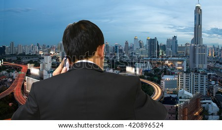 Young business man talking on cell phone and view of the city. - stock photo