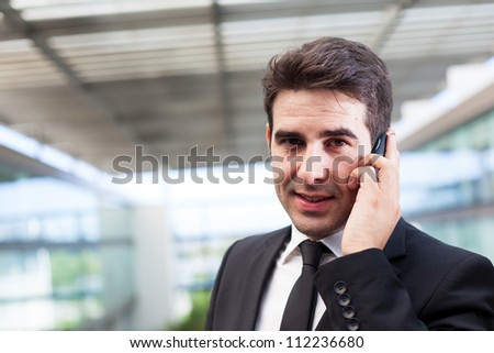 Young business man talking on cell phone at modern office