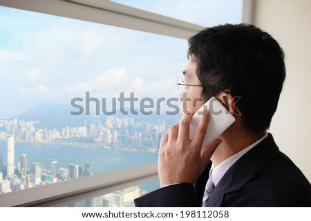 Young business man talking on smart phone in office and look city through window, asia, hong kong, asian - stock photo