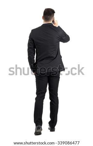 Young business man talking on the phone walking away rear view. Full body length portrait isolated over white studio background.