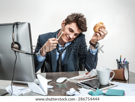 Young business man talking on the phone while holding burger in one hand and pencil in the other looking down smiling / modern office man at working place, sloth and laziness concept - stock photo