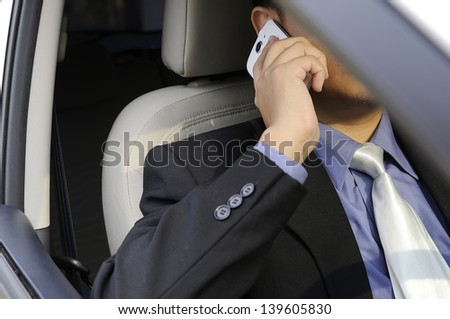 Young business man talking with his cellphone while driving a car - stock photo