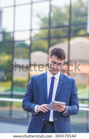 young business man think look up hold tablet pc computer, in bright blue office