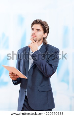 young business man think look up hold tablet pc computer, in bright blue office, businessman executive wear suit pondering - stock photo