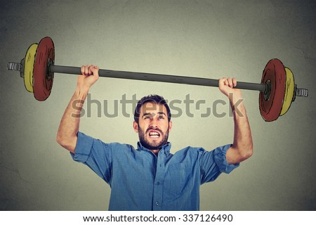 young business man trying to lift very heavy weight. - stock photo