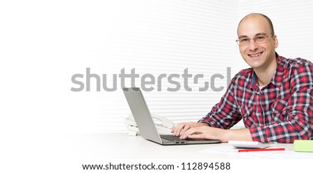 young business man using a laptop at the desk in office