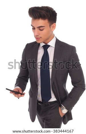 young business man using his smartphone , texting or reading on its screen, isolated on white background