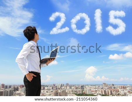 Young business man using laptop and look to 2015 year text with blue sky and cloud and cityscape in the background, asian - stock photo