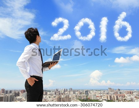 Young business man using laptop and look to 2016 year text with blue sky and cloud and cityscape in the background, asian - stock photo