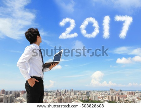 Young business man using laptop and look to 2017 year text with blue sky and cloud and cityscape in the background, asian