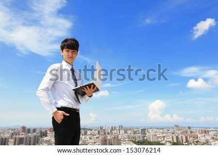 Young business man using laptop and look to you with cityscape in the background, business and cloud computing concept - stock photo