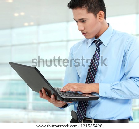 young business man using laptop while standing at the office - stock photo