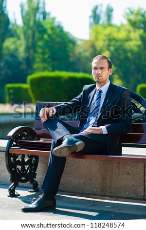 Young business man waiting for meeting at green park - stock photo