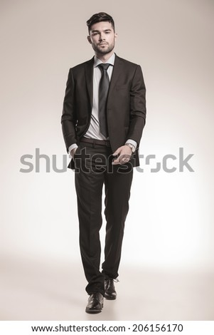 young business man walking forward with one hand in his pocket, studio picture - stock photo