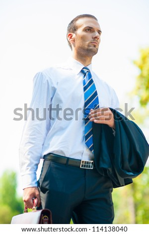 young business man walking in the park - stock photo