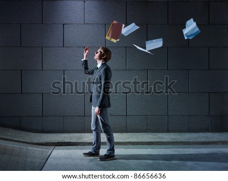 young business man walking out from office parking and throwing away paperworks. Horizontal shape, side view, copy space - stock photo
