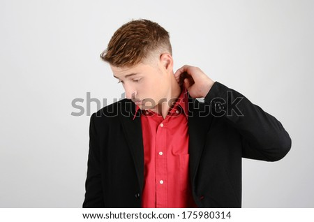 Young business man wearing a suit and a red shirt looking down. Sad, unhappy, stressed. - stock photo