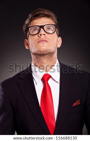 young business man wearing eyeglasses is looking up, on dark background