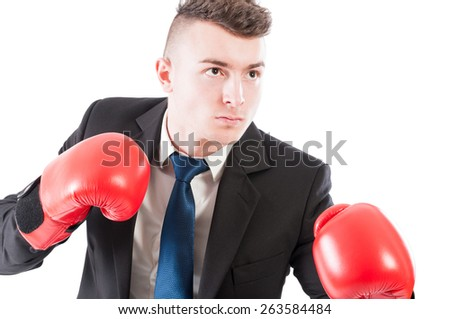 Young business man wearing red boxing gloves ready to punch or fight