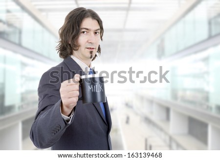 young business man with a cup of milk at the office