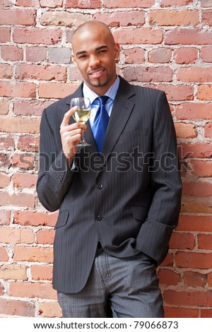 Young business man with a glass of white wine near a brick wall. - stock photo