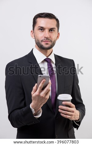 Young business man with a phone and coffee