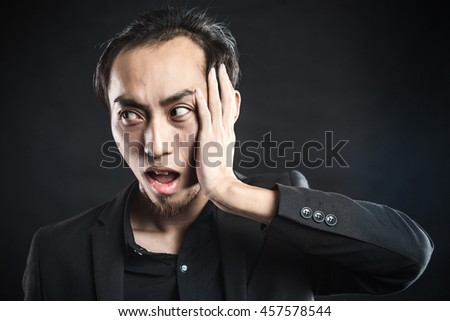 Young business man with a teethache against a black background