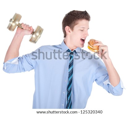 Young business man with dumbbell eating tasty hamburger.